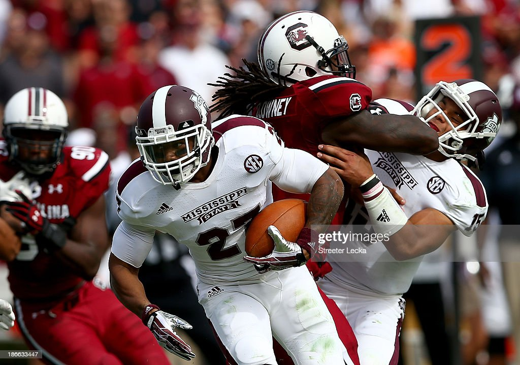 LaDarius Perkins #27 of the Mississippi State Bulldogs runs with the ball as Jadeveon Clowney #7 of the South Carolina Gamecocks hits Dak Prescott #15 during their game at Williams-Brice Stadium on November 2, 2013 in Columbia, South Carolina.