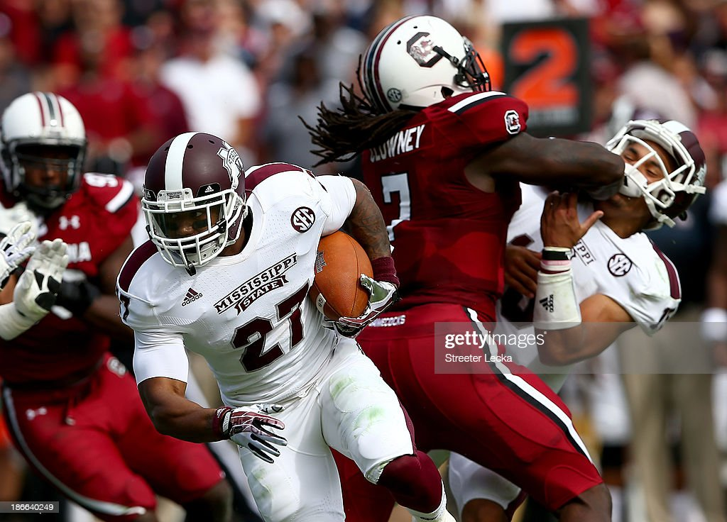 LaDarius Perkins #27 of the Mississippi State Bulldogs runs with the ball as <a gi-track='captionPersonalityLinkClicked' href=/galleries/search?phrase=Jadeveon+Clowney&family=editorial&specificpeople=7471550 ng-click='$event.stopPropagation()'>Jadeveon Clowney</a> #7 of the South Carolina Gamecocks hits Dak Prescott #15 during their game at Williams-Brice Stadium on November 2, 2013 in Columbia, South Carolina.