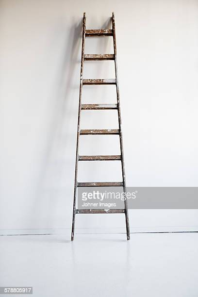 Ladder against white wall