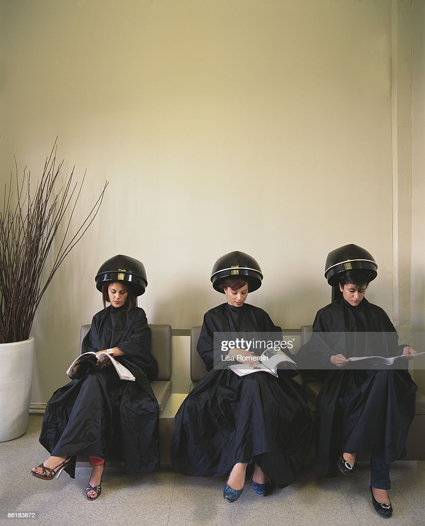 Ladies at salon under hair dryers reading magazine : Stock Photo