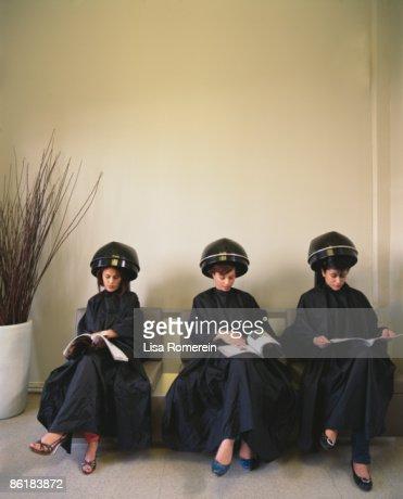 Ladies at salon under hair dryers reading magazine