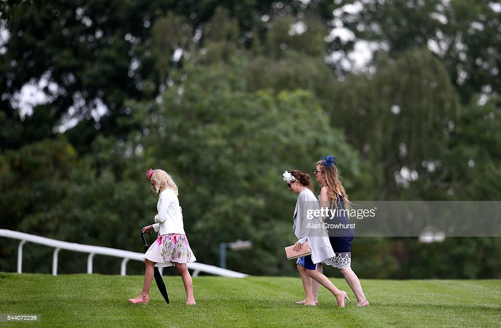 Ladies cross the track at Sandown Park on July 01, 2016 in Esher, England.