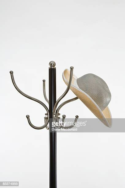 A ladies' hat haning on hat rack on a coat stand