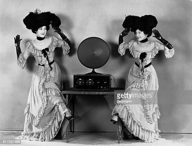 Ladies in long dresses practice polka steps by a radio