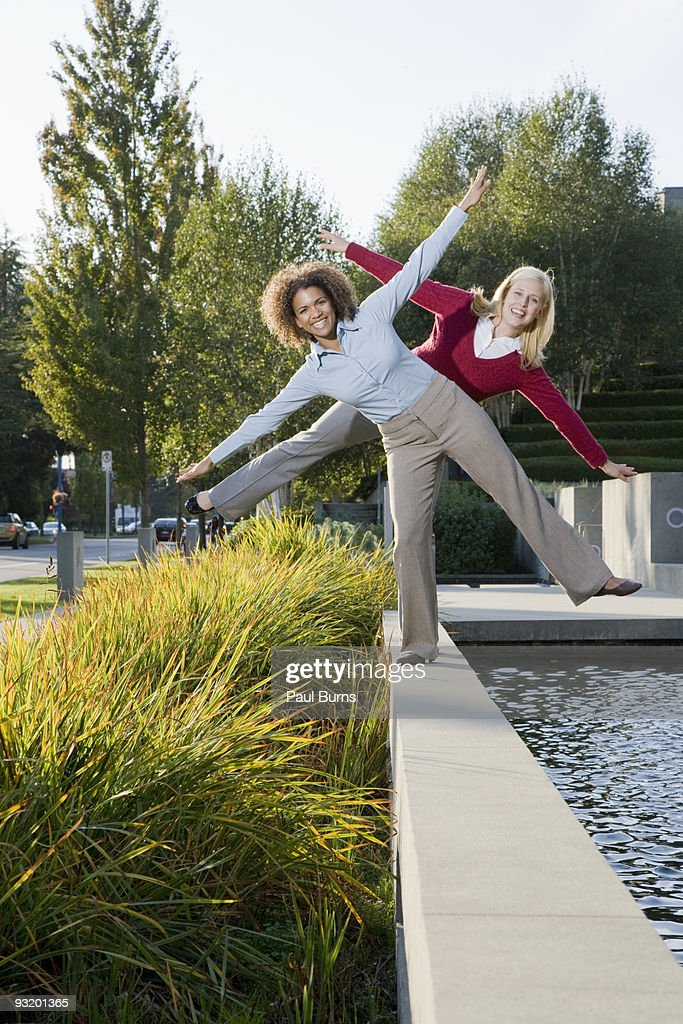 Ladies in suit balancing at fountain side : Stock Photo