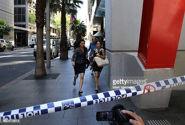 Ladies rush through Philip St past armed police at Lindt Cafe Martin Place on December 15 2014 in Sydney Australia Police attend a hostage situation...