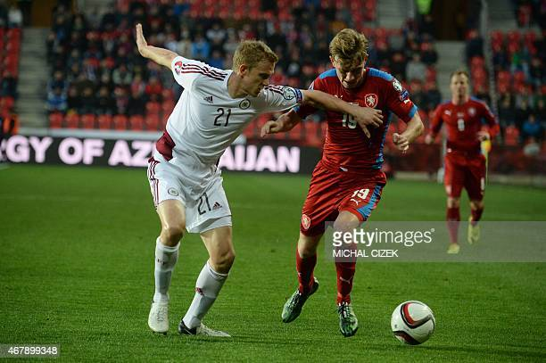 Ladislav Krejci of Czech Republic and Gints Freimanis of Latvia vie for the ball during the Group A Euro 2016 qualifying football match between Czech...
