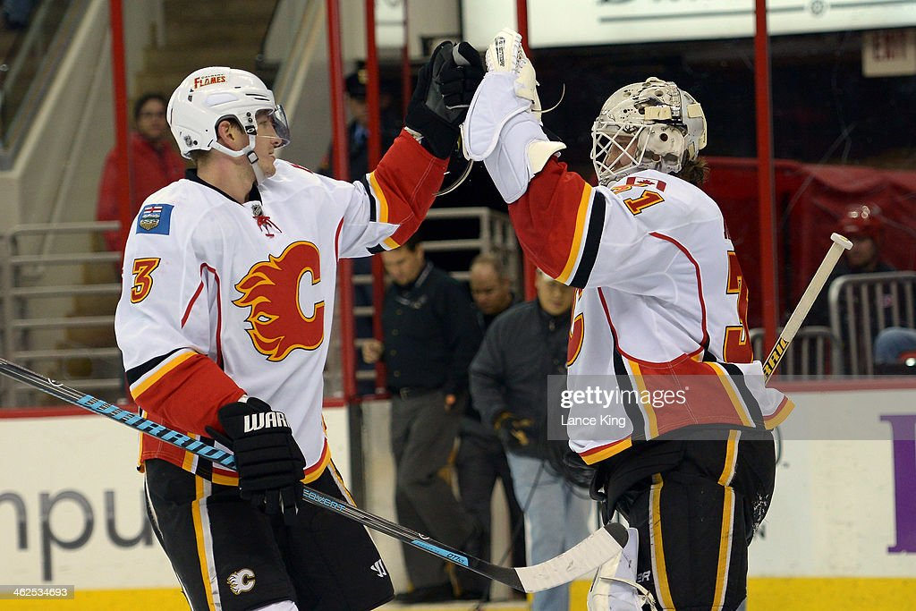 Ladislav Smid #3 and <a gi-track='captionPersonalityLinkClicked' href=/galleries/search?phrase=Karri+Ramo&family=editorial&specificpeople=716721 ng-click='$event.stopPropagation()'>Karri Ramo</a> #31 of the Calgary Flames celebrate following their game against the Carolina Hurricanes at PNC Arena on January 13, 2014 in Raleigh, North Carolina. The Flames defeated the Hurricanes 2-0.
