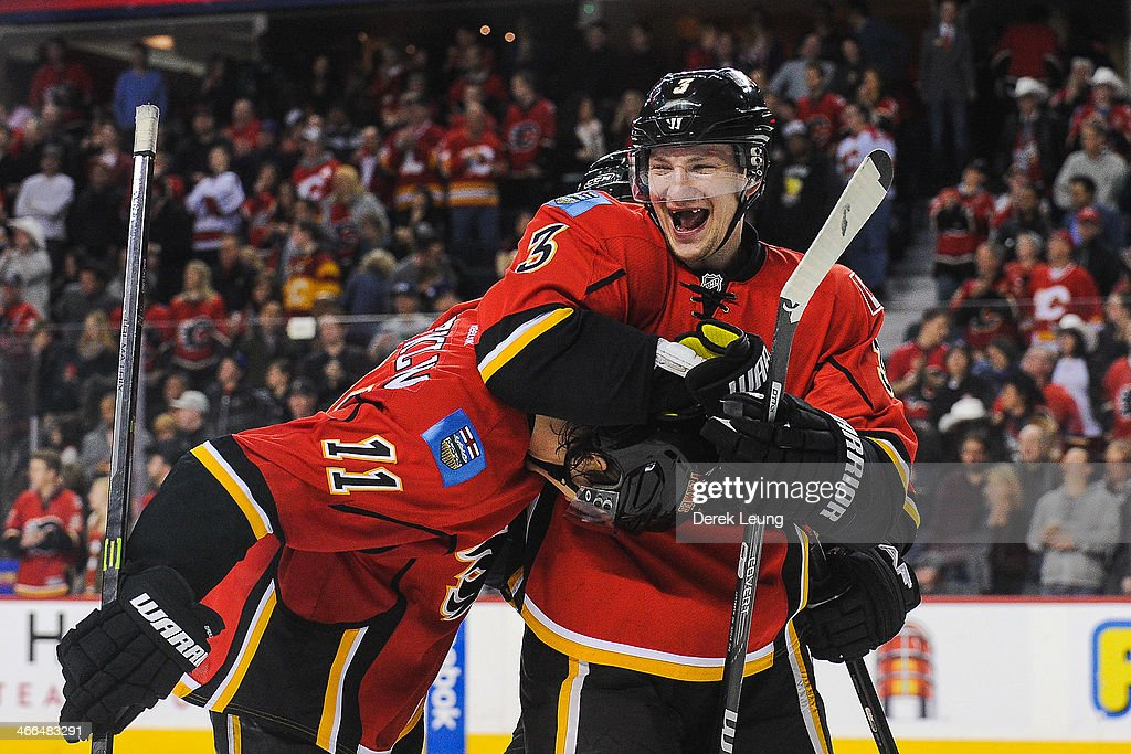 Ladislav Smid congratulates Mikael Backlund of the Calgary Flames after Mikael Backlund scored the gamewinning goal against the Minnesota Wild during...