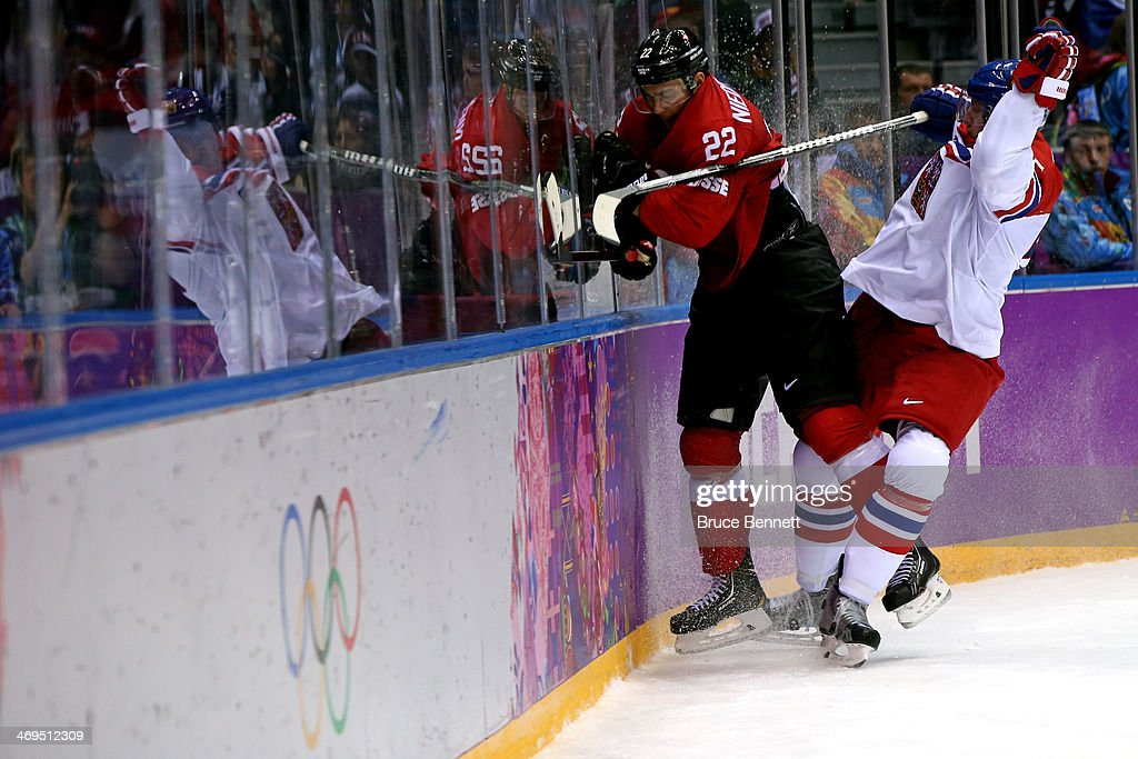 Ladislav Smid of Czech Republic checks Nino Niederreiter of Switzerland into the boards during the Men's Ice Hockey Preliminary Round Group C game on...