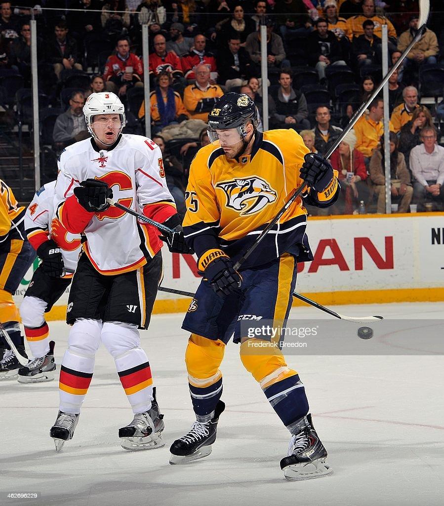Ladislav Smid of the Calgary Flames and Colin Wilson of the Nashville Predators react as a puck flies toward them at Bridgestone Arena on January 14...