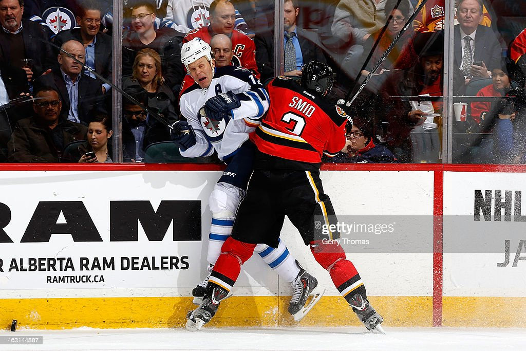 Ladislav Smid #3 of the Calgary Flames checks <a gi-track='captionPersonalityLinkClicked' href=/galleries/search?phrase=Olli+Jokinen&family=editorial&specificpeople=202946 ng-click='$event.stopPropagation()'>Olli Jokinen</a> #12 of the Winnipeg Jets at Scotiabank Saddledome on January 16, 2013 in Calgary, Alberta, Canada.