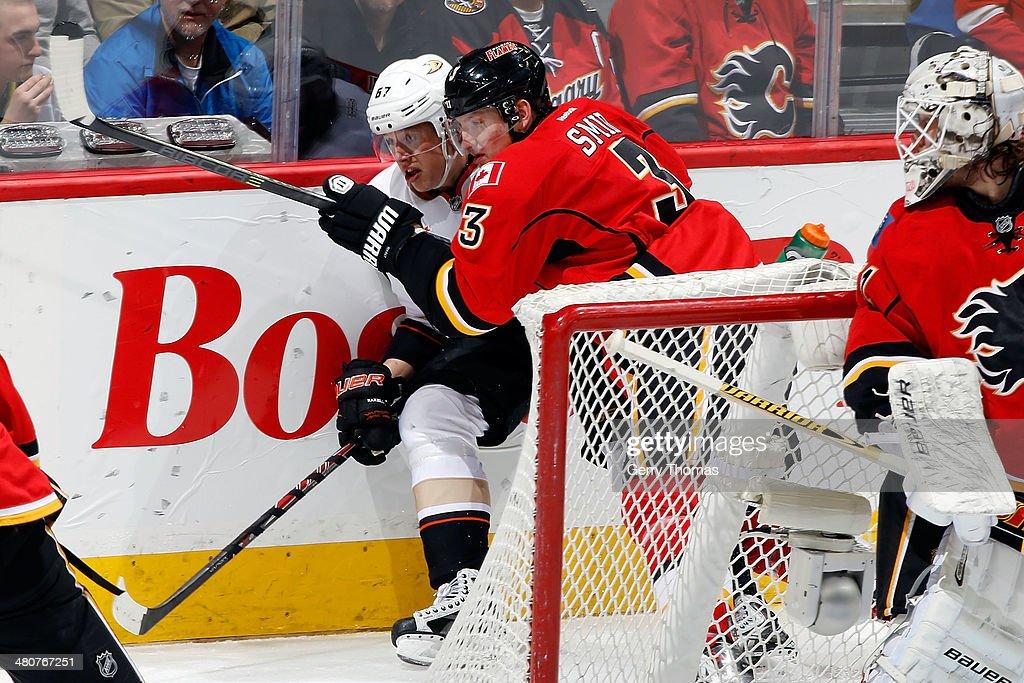 Ladislav Smid of the Calgary Flames checks Rickard Rackell of the Anaheim Ducks at Scotiabank Saddledome on March 26 2014 in Calgary Alberta Canada