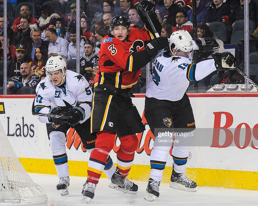 Ladislav Smid #3 of the Calgary Flames collides with Tommy Wingels #57 (L) and Patrick Marleau #12 of the San Jose Sharks during an NHL game at Scotiabank Saddledome on March 24, 2014 in Calgary, Alberta, Canada.