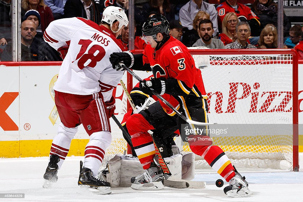 Ladislav Smid of the Calgary Flames skates against David Moss of the Phoenix Coyotes at Scotiabank Saddledome on December 4 2013 in Calgary Alberta...
