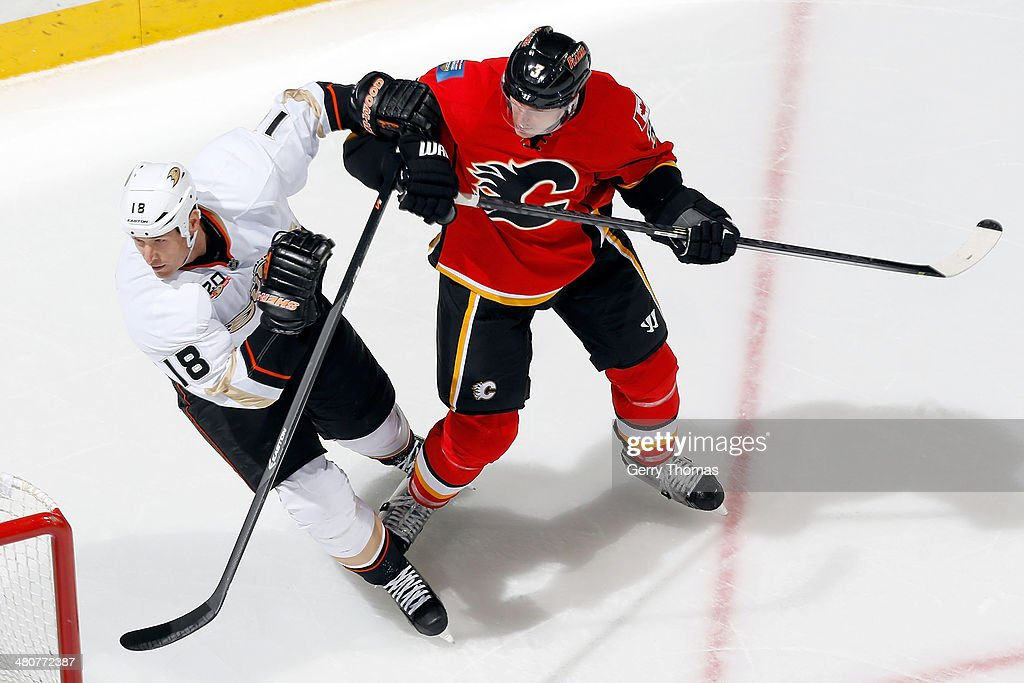 Ladislav Smid of the Calgary Flames skates against Tim Jackman of the Anaheim Ducks at Scotiabank Saddledome on March 26 2014 in Calgary Alberta...