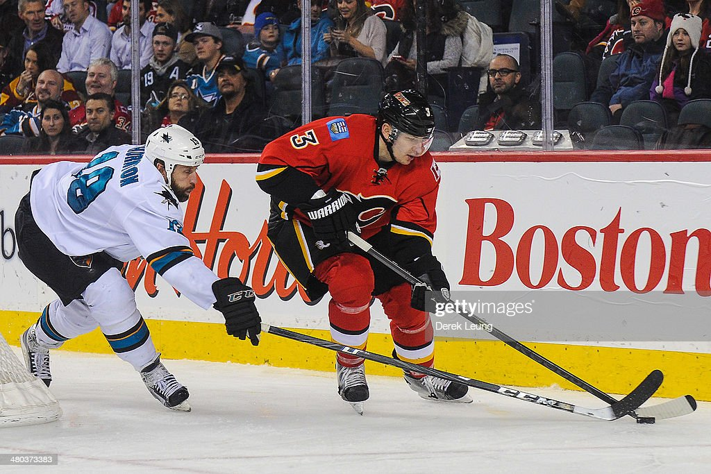 Ladislav Smid #3 of the Calgary Flames skates with the puck against Joe Thornton #19 of the San Jose Sharks during an NHL game at Scotiabank Saddledome on March 24, 2014 in Calgary, Alberta, Canada.