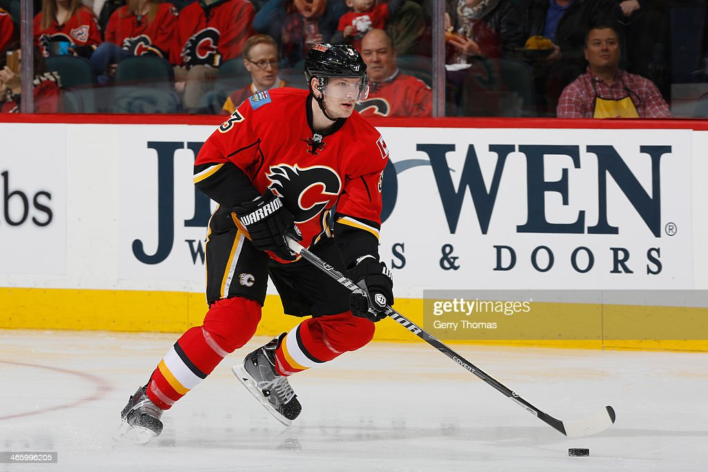 Ladislav Smid of the Calgary Flames skates with the puck in a game against the San Jose Sharks at Scotiabank Saddledome on January 30 2014 in Calgary...