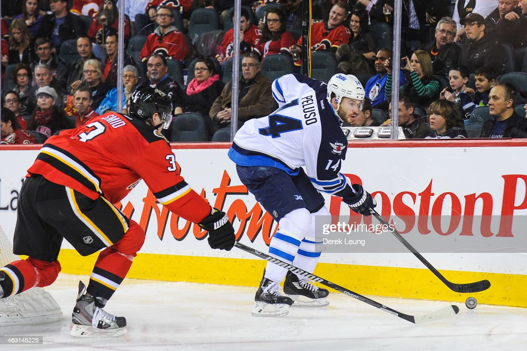 Ladislav Smid #3 of the Calgary Flames tries to check Anthony Peluso #14 of the Winnipeg Jets during an NHL game at Scotiabank Saddledome on January 16, 2014 in Calgary, Alberta, Canada.