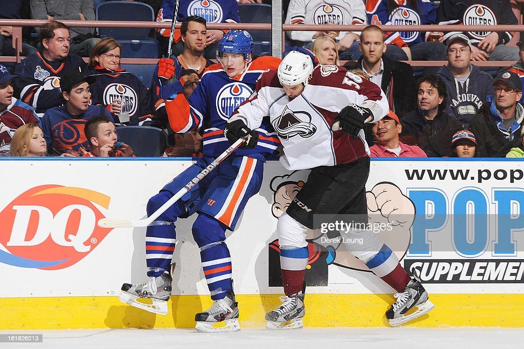 Ladislav Smid #5 of the Edmonton Oilers gets flattened against the boards by Patrick Bordeleau #58 of the Colorado Avalanche during the NHL game at Rexall Place on February 16, 2013 in Edmonton, Alberta, Canada.