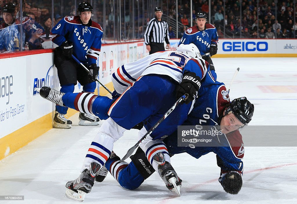 Ladislav Smid of the Edmonton Oilers puts a hit on Jamie McGinn of the Colorado Avalanche at the Pepsi Center on April 19 2013 in Denver Colorado