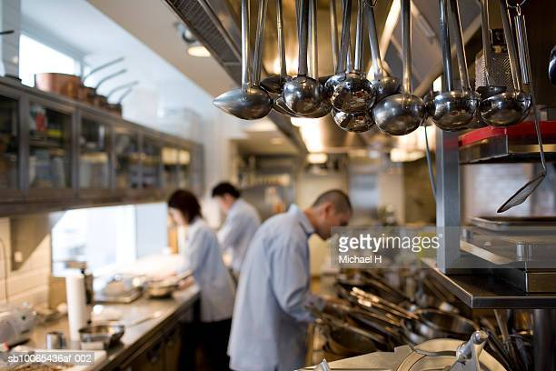 Ladles hanging in kitchen, three chefs in background