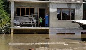 A lady along with a girl standing in the second floor of the house as their houses are submerged in flood waters on September 11 2014 in Srinagar...