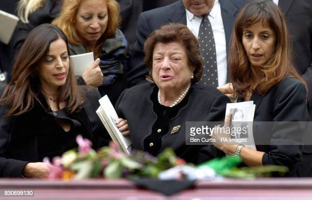Lady Anna Stakis widow of Sir Reo Stakis is helped down the steps by mourners as she looks at the coffin of her husband as it is carried out of the...