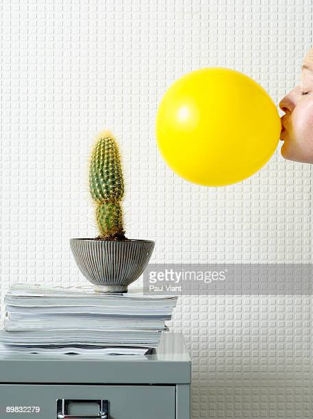 lady blowing up balloon next to cactus