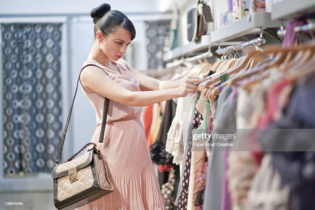 lady browsing through a clothes rail of dresses : Stock Photo