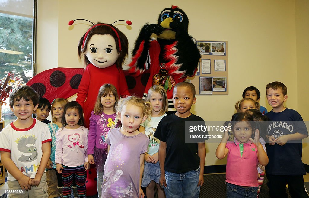 Lady Bug Girl and Tommy Hawk pose with children at Bright Horizons on October 4, 2012 in Chicago, Illinois.
