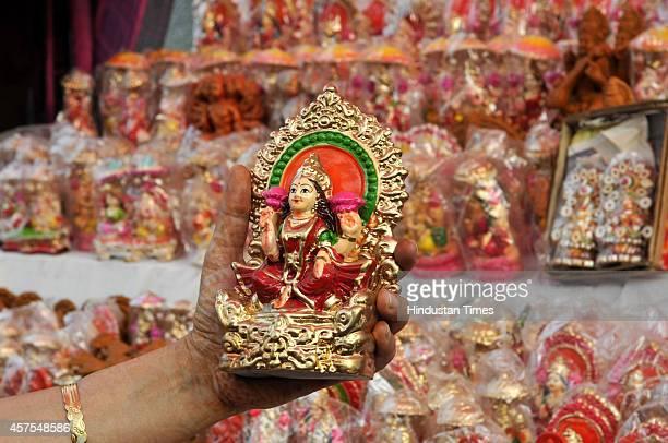 A lady buy idols of Goddess Laxmi and Lord Ganesha from roadside stalls ahead of Hindu festival Diwali at Sarojni Nagar Market on October 20 2014 in...
