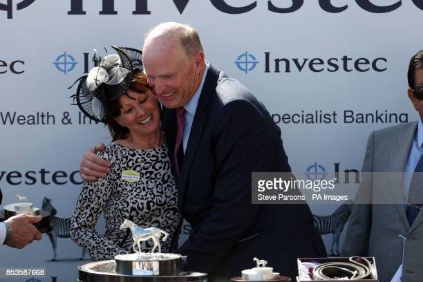 Lady Cecil present winning trainer John Gosden who trained Taghrooda ridden by Paul Hanagan to win the Investec Oaks during Investec Ladies Day at...