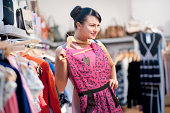 lady checking out printed pink dress in a shop