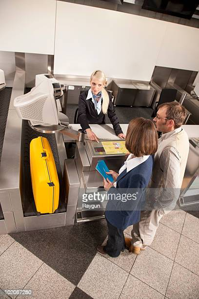 Lady checking the weight of a suitcase