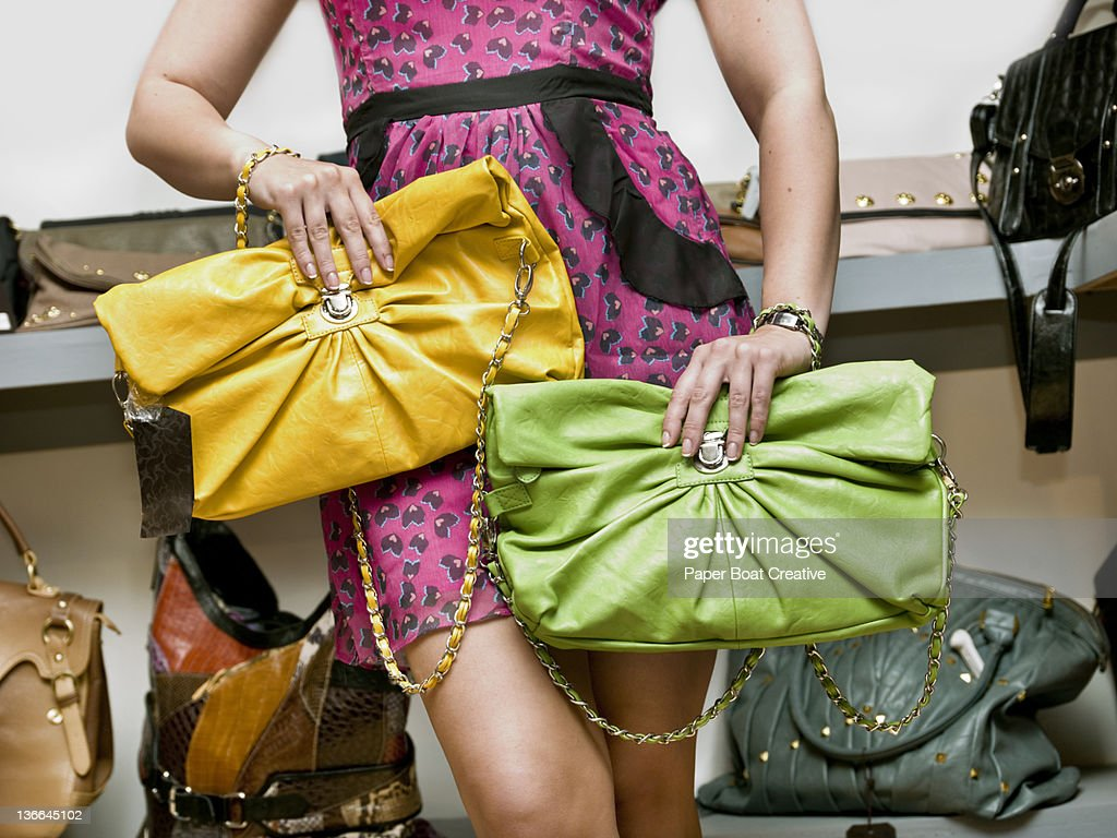 lady choosing between two colorful clutch bags : Stock Photo