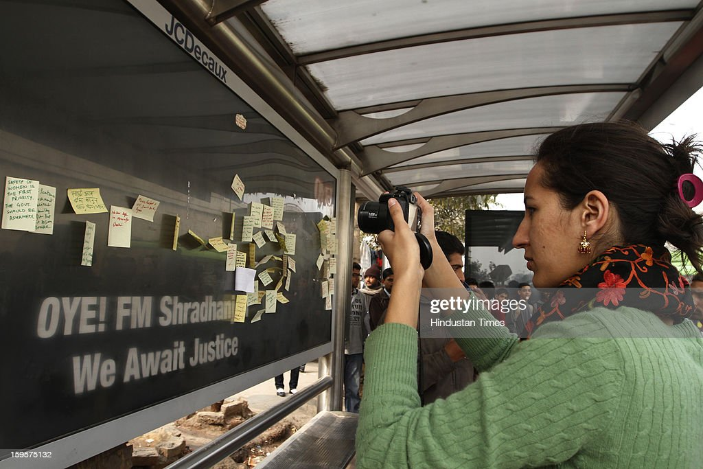 A lady clicks the sentiments written by the students and people, for the victim of the gang rape on bus stand at Munirka on January 16, 2013 in New Delhi, India. It is the same spot from where the victim boarded that unfortunate bus exactly one month ago.