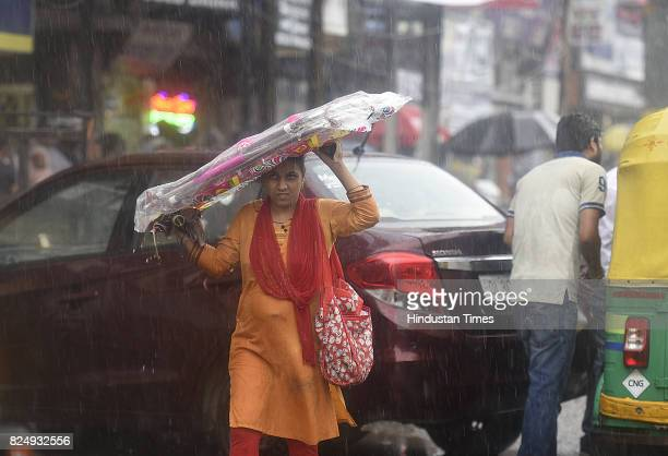 A lady covers herself from the rain during the monsoon rain on July 31 2017 in New Delhi India Delhiites woke up to a drenched morning as rains hit...