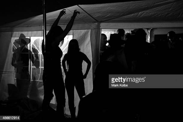 A lady dances on a pole as campers party late in the night outside a DJ tent setup in the 'Ute Paddock' on the first day of the 2014 Deni Ute Muster...