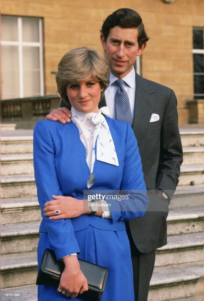 Lady Diana Spencer (later to become Princess of Wales) reveals her sapphire and diamond engagement ring while she and Prince Charles, Prince of Wales pose for photographs in the grounds of Buckingham Palace following the announcement of their engagement