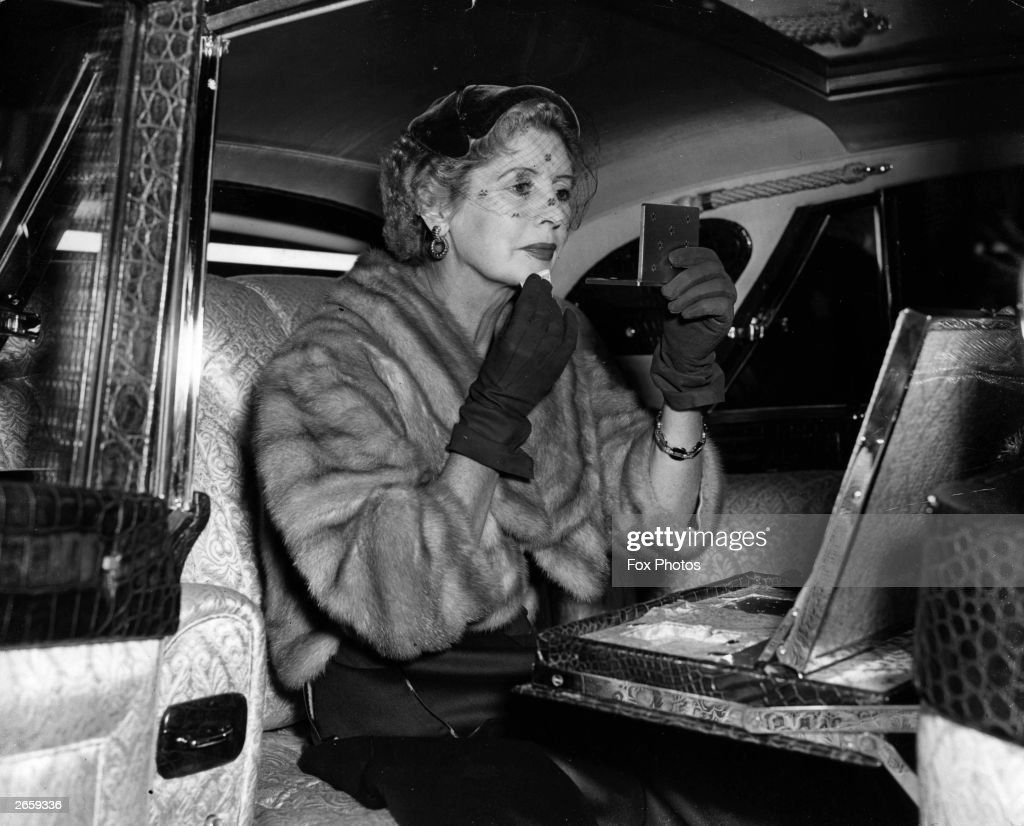 Lady Docker touches up her make-up in her 'Stardust' Daimler, a new model which was unveiled at the Earl's Court motor show.