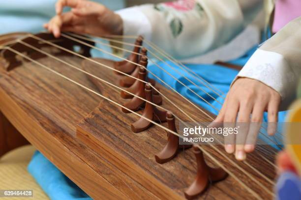 Lady dressed in hanbok plays the traditional Korean musical instrument(gayageum)