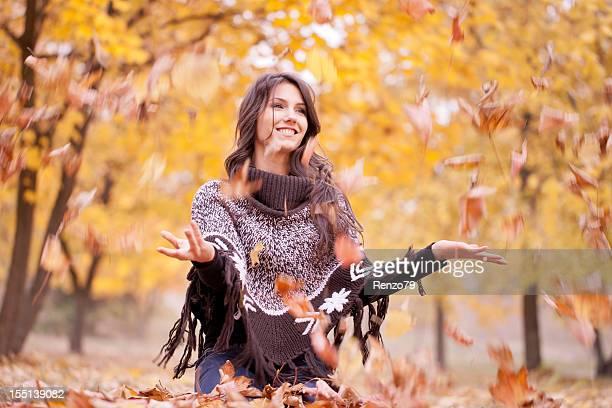 Junge Frau sitzt im Herbst wood