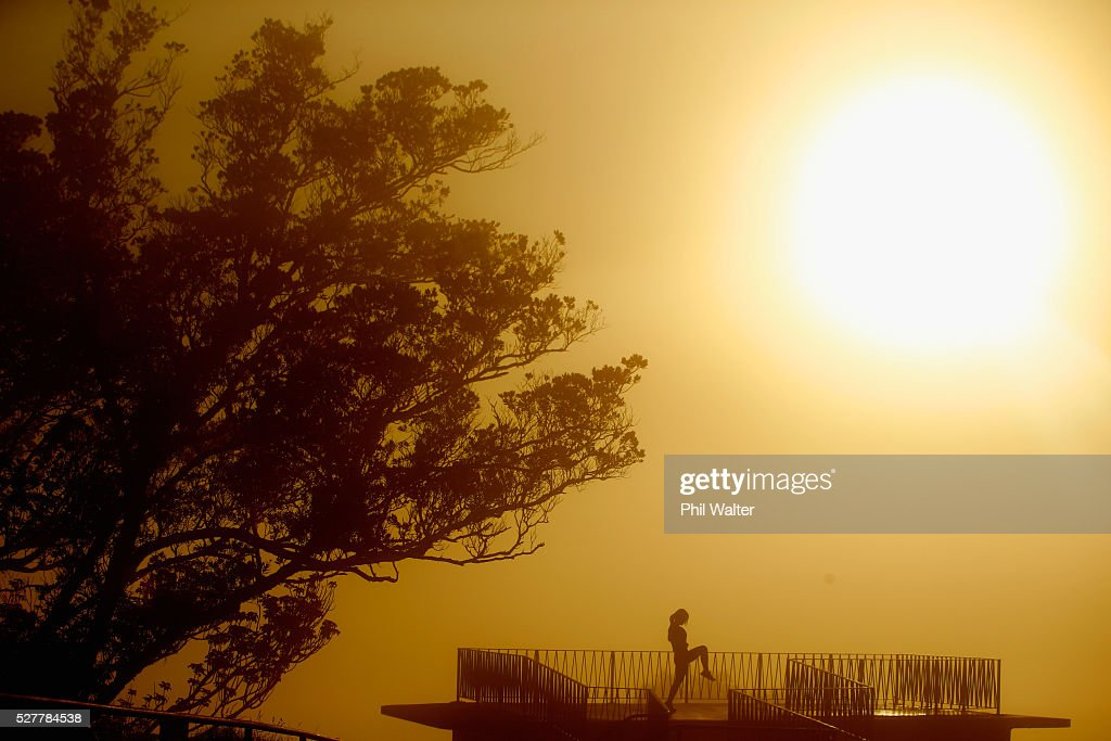 A lady exersises on the summit of Mt Eden as the sun struggles to shine through a blanket of fog over Auckland City on May 4, 2016 in Auckland, New Zealand. The morning fog disrupted flights and ferry services in the city.
