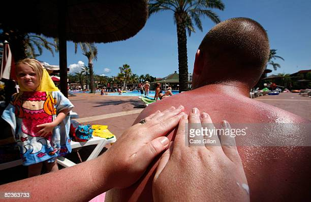 A lady from Northern Ireland puts sun tan lotion on her husband's back at the Costa Encantada hotel on August 15 2008 in Lloret de Mar Spain The...