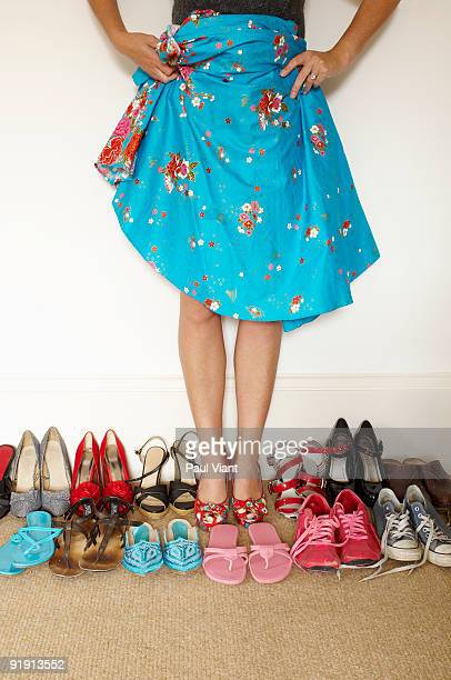 lady holding up skirt surrounded by shoes
