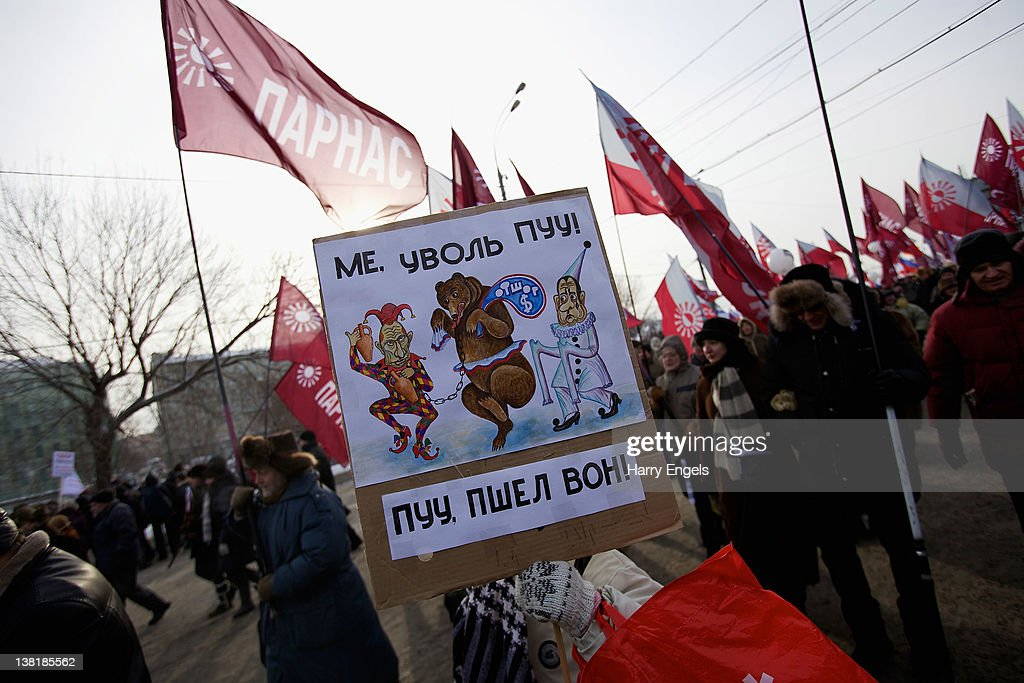 A lady holds a sign that pictures Vladimir Putin as a jester leading a bear, Dmitry Medvedev, by a chain and reads 'Putin, get out!' on February 4, 2012 in Moscow, Russia. Demonstrators braved temperatures as low as -20 degrees celsius as they took to the streets exactly one month before the presidential elections in protest against Vladimir Putin's efforts to return to the Kremlin for an unprecedented third term as President.