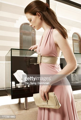 A lady in a pink dress going jewelry shopping