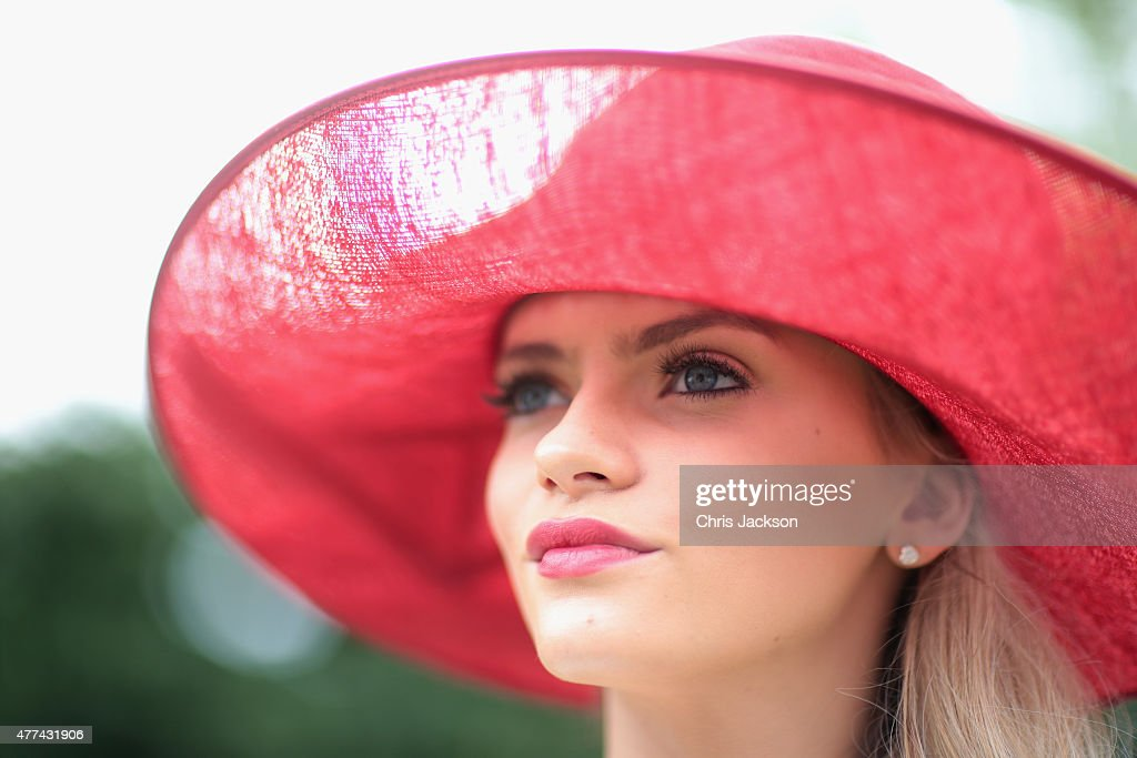 A lady in a red hat arrives for day 2 of Royal Ascot at Ascot Racecourse on June 16 2015 in Ascot England