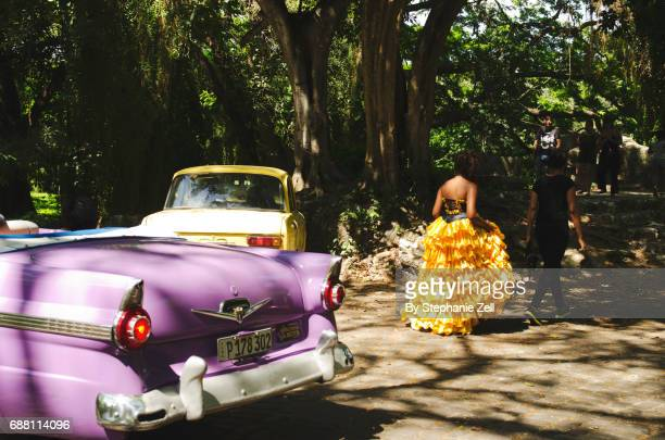 Lady in a ruffled quinceanera dress walking past vintage car in a cuban park